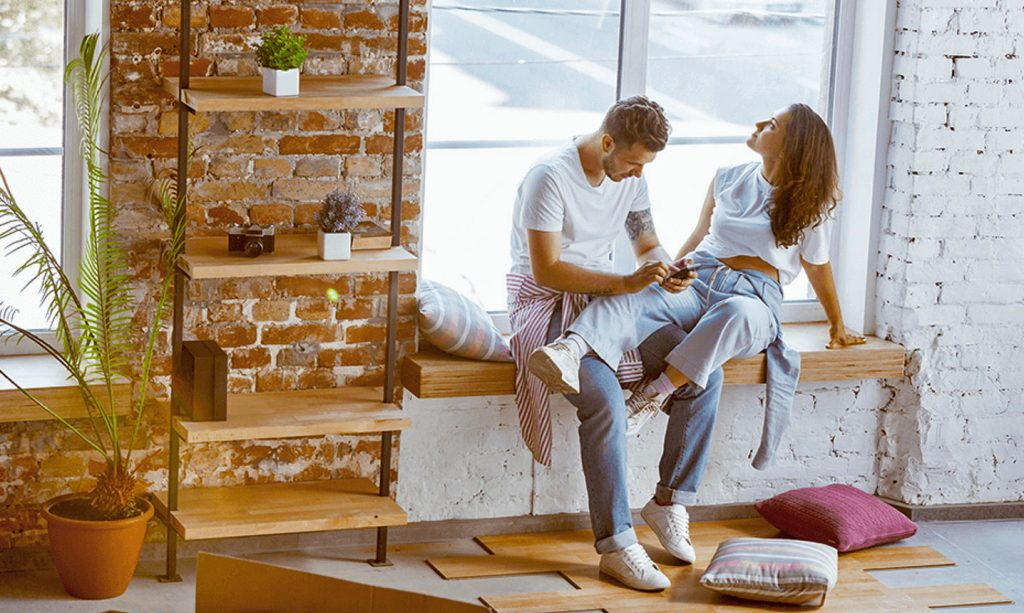 Couple sit on a window sill reviewing their options on a smart phone